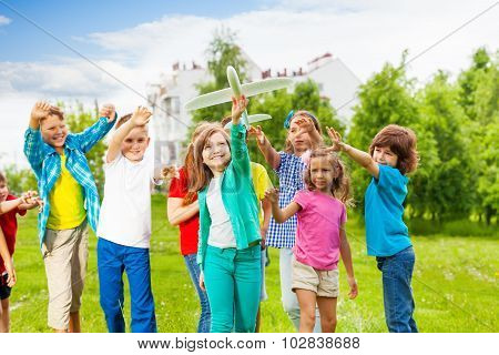 Girl holding big airplane toy and children behind