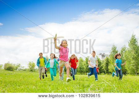 Small girl holding airplane toy and kids behind