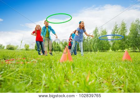 Two group of kids play throwing colorful hoops