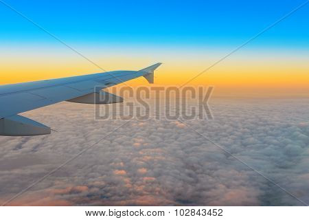 Airplane wing out of window at sunrise