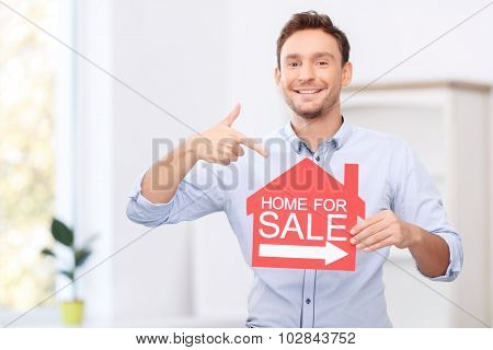 Pleasant realtor holding card