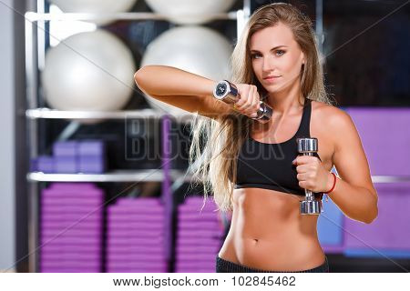 Young slim girl with long hair wearing in black top and breeches holding dumbbells in her hands on the sport equipment background in the gym waist up
