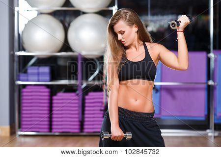 Beautiful fitness girl with long hair wearing in black top and breeches posing with dumbbells on the sport equipment background in the gym waist up
