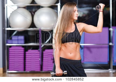 Strong brunette girl with long hair wearing in black top and breeches holding dumbbells on the sport equipment background in the gym waist up