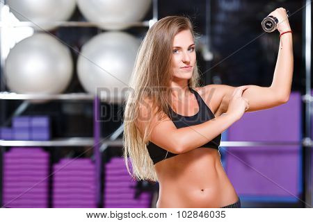 Attractive muscled girl with long hair wearing in black top and breeches posing with dumbbells on the sport equipment background in the gym waist up