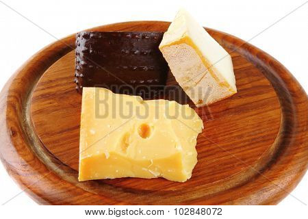 solid french delicatessen cheeses on wooden plate