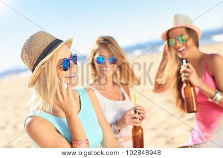 A picture of a group of friends drinking beer and talking on the phone on the beach