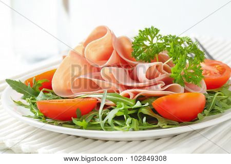 plate of fresh arugula leaves with sliced ham and halved tomatoes