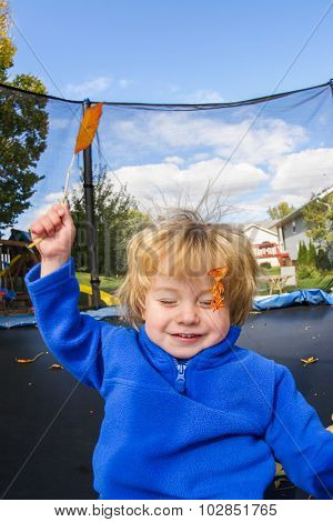 Smiling boy jumping and catching an autumn leaf on a trampoline,  some motion blur.