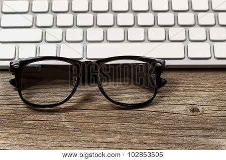 Hipster Reading Glasses With Keyboard On Rustic Wooden Desktop