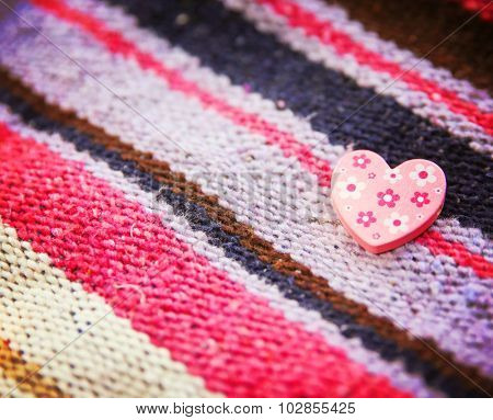 a wooden heart with tiny flowers on it on a blanket background