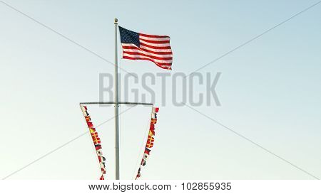 American Flag And Nautical Flags On Ship's Mast