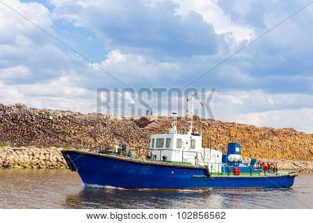 Lightweight ship moving by the harbor channel of Liepaja