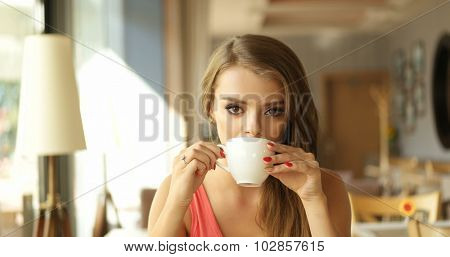 Close Up of Young Woman Sipping Coffee from White Mug in Sunny Window Seat of Trendy Cafe Restaurant with Copy Space