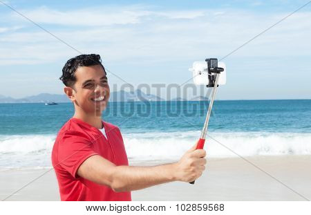 Latin Guy At Beach Talking A Picture With His Phone And Selfie Stick