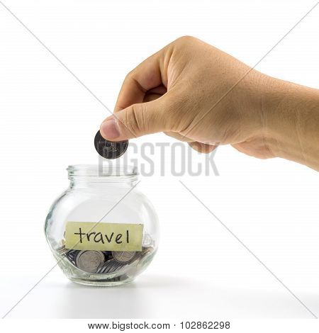 Hand Putting Coin Into Glass Container With  Travel Label On White Background. Selective Focus.