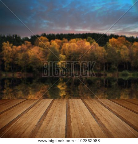 Beautiful Vibrant Autumn Woodland Reflecions In Calm Lake Waters Landscape With Wooden Planks Floor