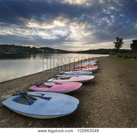 Summer Sunset Over Lake In Landscape With Leisure Boats And Equipment On Shore