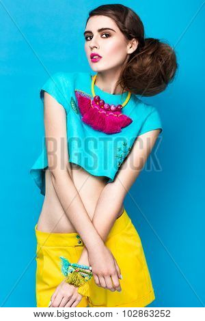 Beautiful fashionable woman an unusual hairstyle in bright clothes and colorful accessories.