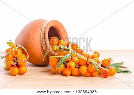 Berries Are Scattered Out Of A Ceramic Pot On A Wooden Background