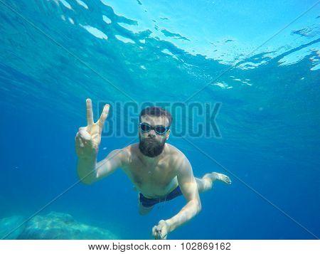 Man Doing Underwater Selfie Shot With Selfie Stick In Deep Sea