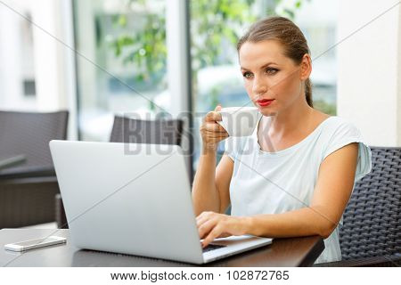 Young Business Woman Sitting In A Cafe With A Laptop And Drinks Her Morning Coffee