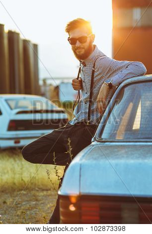 Portrait Of A Young Handsome Stylish Man, Wearing Shirt And Bow-tie With Old Cars
