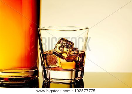 Glass Of Whiskey With Ice Cubes Near Bottle On Table With Reflection, Warm Tint Atmosphere