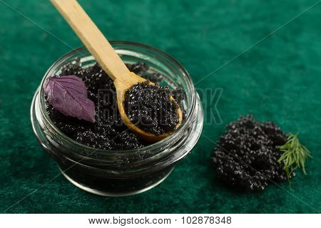Black Beluga Caviar In A Glass Jar On A Green Fabric Background