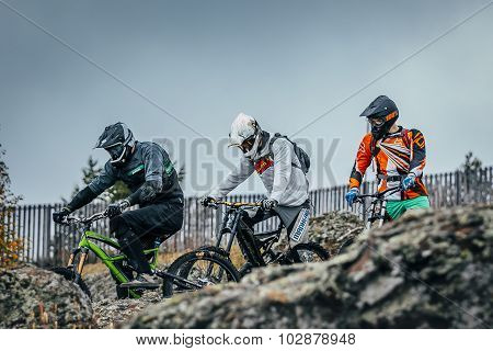 riders downhill bikes prepare to descend