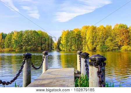 View From Dock On Lake And Multicolored Trees In The Urban Park In Autumn Season