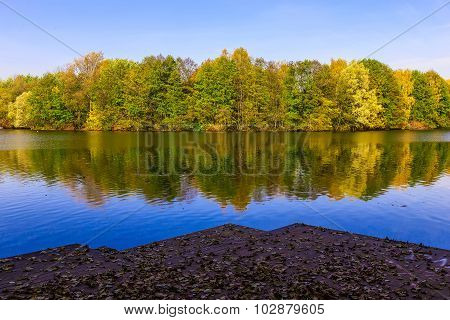 View From Pier On Lake And Multicolored Trees In The Public Park In Autumn Season