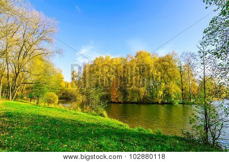 Autumn Scenery With Colourful Trees, Green Grass Near Lake