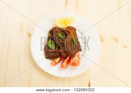 Roast Pork On White Plate On Wooden Background With Vegetables And Herbs