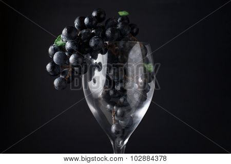 Grapes In Red Wine Glass Hanging Over Against Dark Background