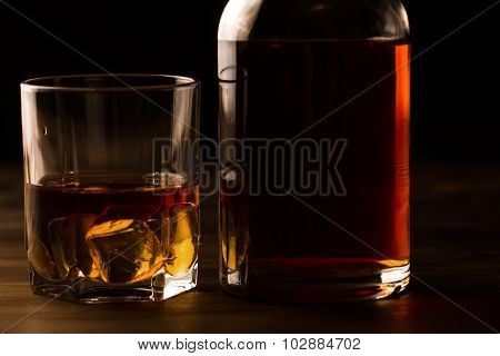 Glass Of Whiskey With Ice And A Bottle On A Wooden Table. Cognac, Brandy.