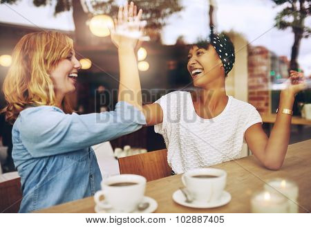 Happy Exuberant Girl Friends Giving A High Five