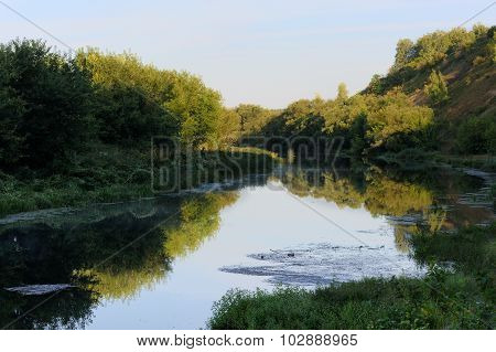 Quiet Small River With Green Trees On Both Banks In Early Summer Morning