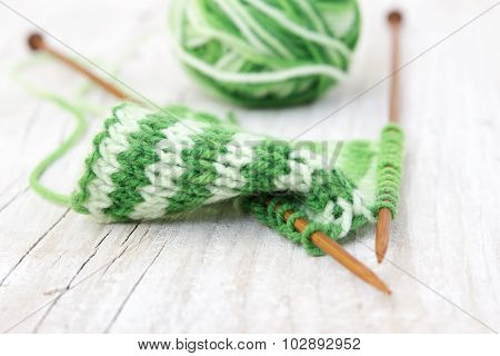 Knitting Pattern Of Green Yarn On Wooden Needles And Skein