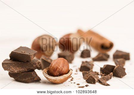 Broken Chocolate Bar, Hazelnut And Cinnamon On Wooden Background, Close-up