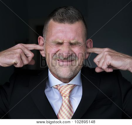 Portrait Of Businessman With Fingers In His Ears