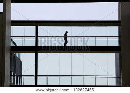 Silhouette view of young businessman in a modern office building interior with panoramic windows.