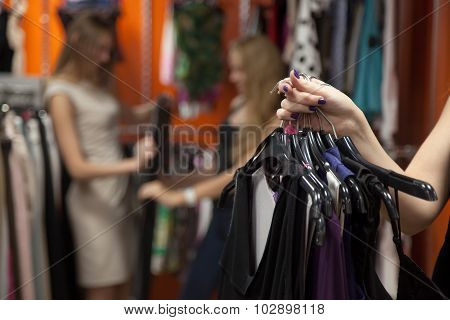 Woman Holding Bunch Of Garments In Shop, Closeup