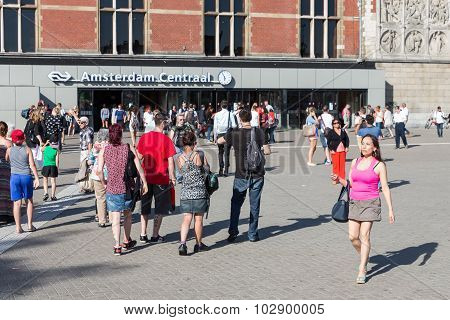 Tourists Walking In Front Of The Central Station Of Amsterdam