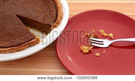 Plate With Crumbs Next To A Sliced Pumpkin Pie