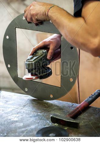 Metalworker Sanding A Metal Component