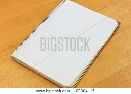 Notebook On Wood Background.