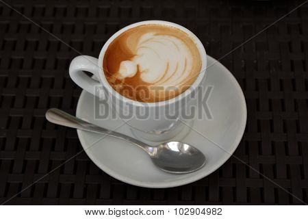 Delicious foamy cappuccino on the black background