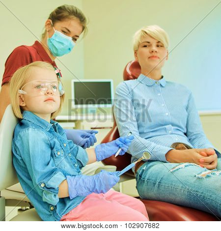 Little cute girl sitting in chair at dentist
