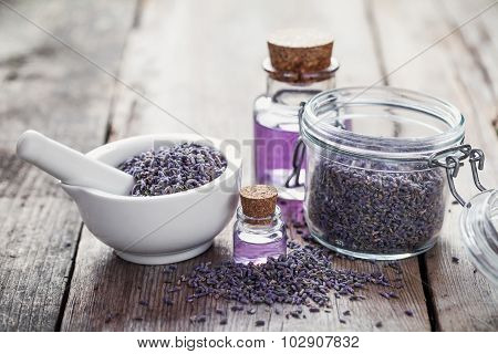Dry Lavender Flowers In White Mortar, Glass Jar Of Lavender And Bottles Of Essential Oil.  Selective